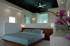 The main bedroom in Gracehaven Villa with a platform bed- Two balconies