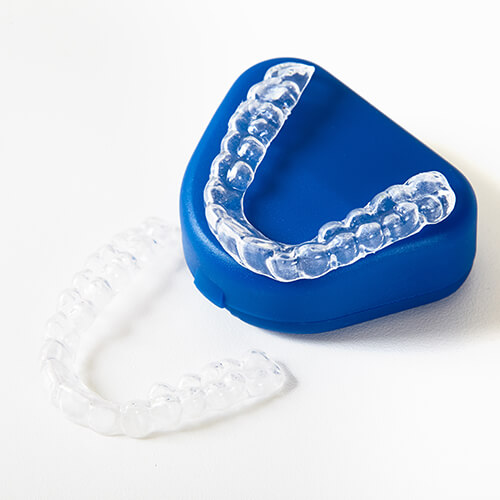Two Invisalign aligners - one on top of the blue box that the aligners arrive in and the other placed on a white surface