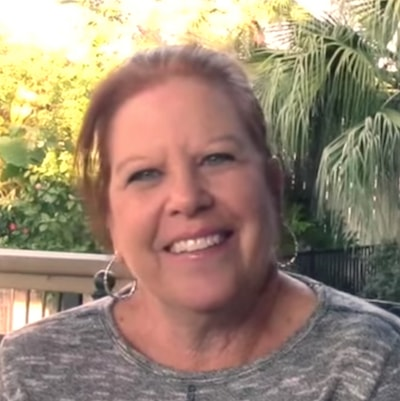 Older lady with ginger hair and hooped earrings smiling with her new smile courtesy of Invisalign®
