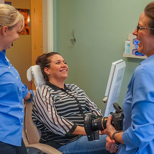 One of our patients smiling in the dentist chair while two team members make her feel comfortable and part of the family