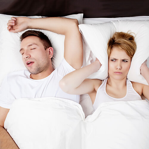 Man sleeping and snoring next to his wife while she holds a pillow over her ears