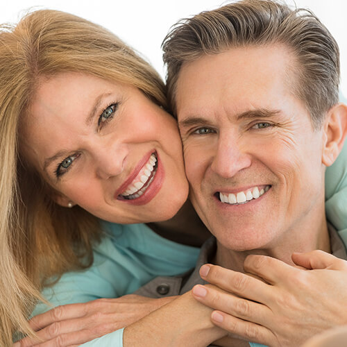 Middle-aged couple hugging and smiling after their fluoride treatment