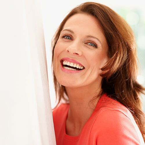 Older lady with dark hair leaning on a wall and smiling after feeling younger from dermal fillers