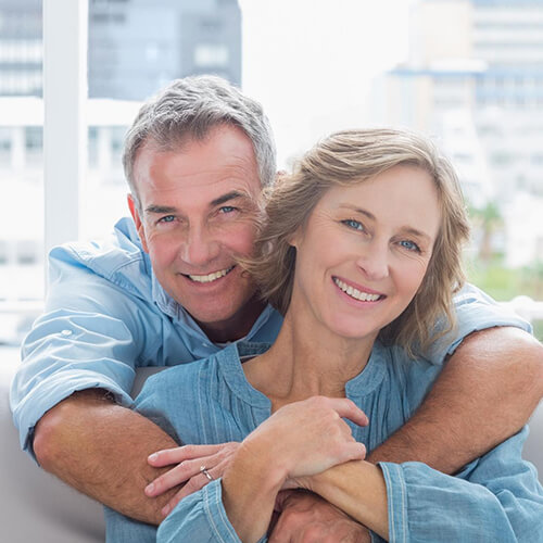 Couple in blue hugging and smiling after their implant dentistry in Houston