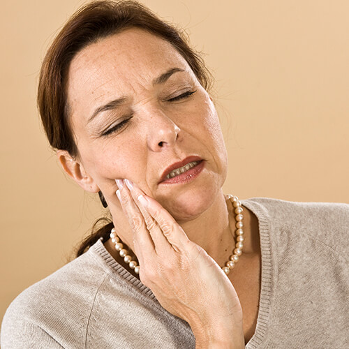 Older lady holding her jaw because of pain caused by TMJ