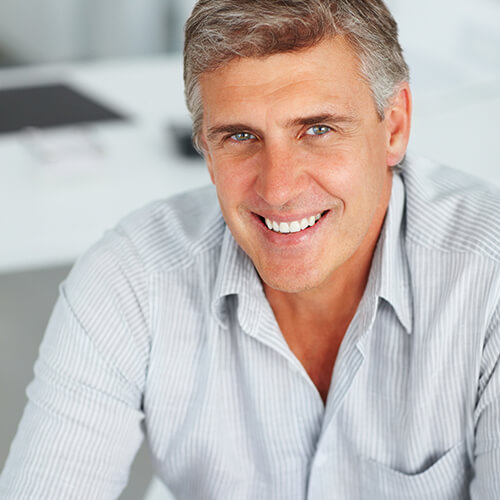 Older gentleman wearing a shirt and smiling after his gum contouring from Dr. Mitchmore