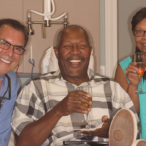 Dr. Mitchmore, Phillip, and his wife sitting by the dentist chair and smiling after a successful full mouth reconstruction