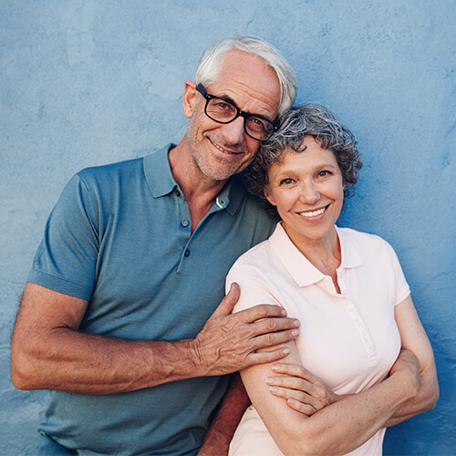 Older couple smiling and standing side-by-side as they contemplate the enjoyable visit they have had at LifeSmiles