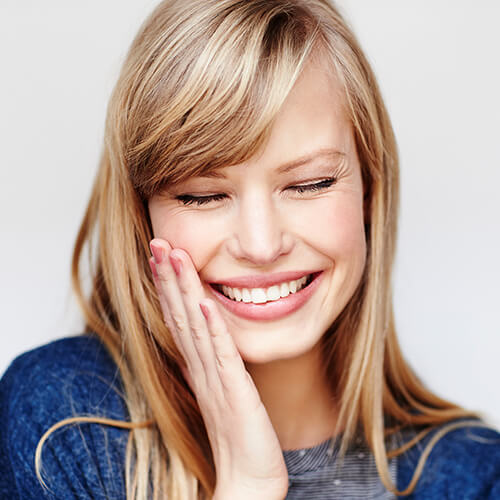 Blonde lady with her eyes shut, smiling, and touching her cheek with her right hand