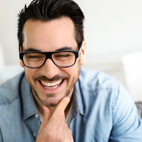 Man wearing glasses with his hand on his chin as he smiles after root canal therapy