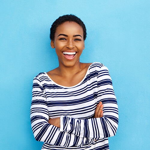 Girl with short hair laughing in front of a blue wall because of the top-class care she has received at LifeSmiles