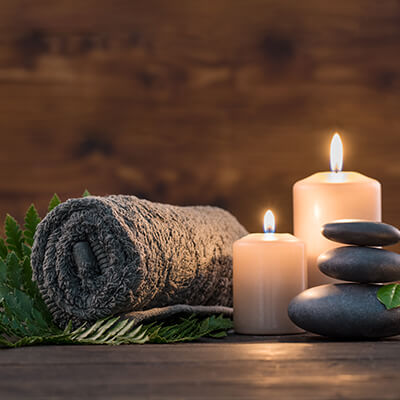 A towel, candles, and smooth stones designed to make your visit relaxing