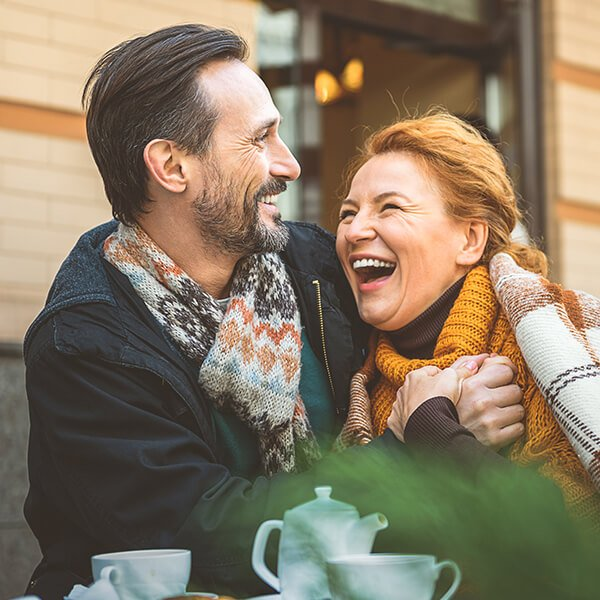 Man with a beard and a woman with red hair hugging and laughing to show that this Houston dentist offers everything you need under one roof.