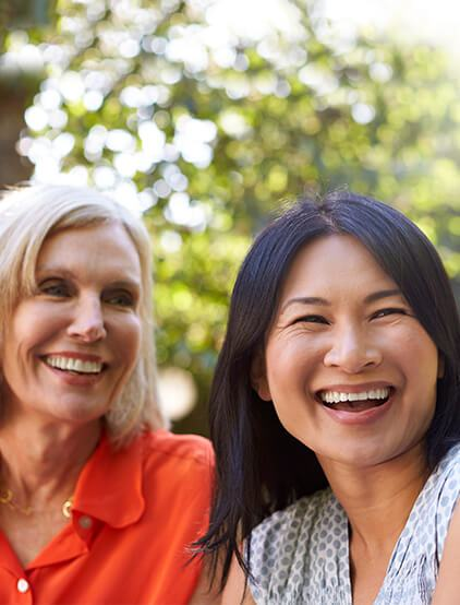 Shot of two woman laughing thanks to Life Smiles services
