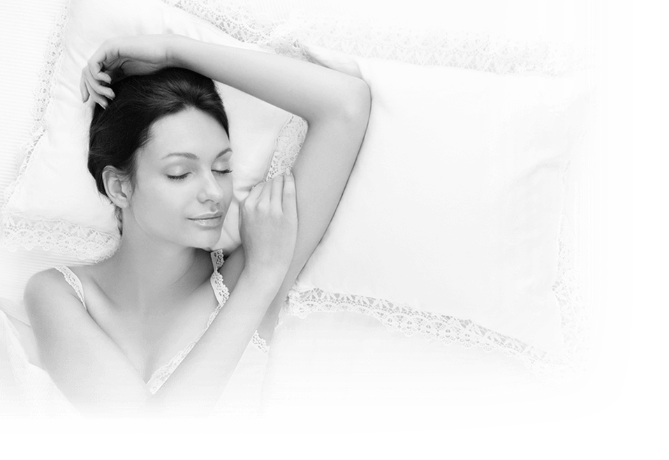 A woman sleep on a pillow with her arms above her head in black and white to illustrate this Houston dentist offers Sedation dentistry