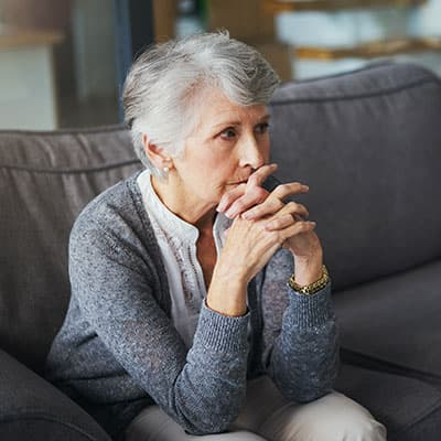 An older Caucasian woman with her hands folded and hiding her mouth, unable to eat her favorite foods cause of missing teeth