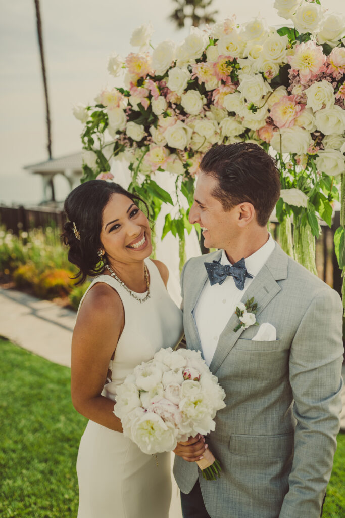 arch floral with bride and groom smiling
