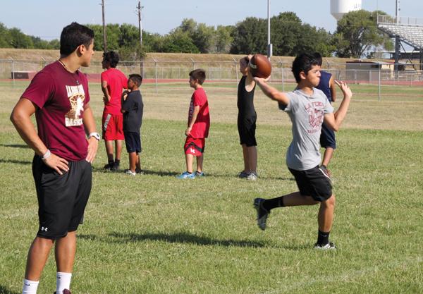 Varsity Quarterback Eric Cuervo instructs some quarterback hopefuls.