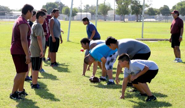 Coach Robert Saucedo oversees offensive line drills. Photos: David Briones