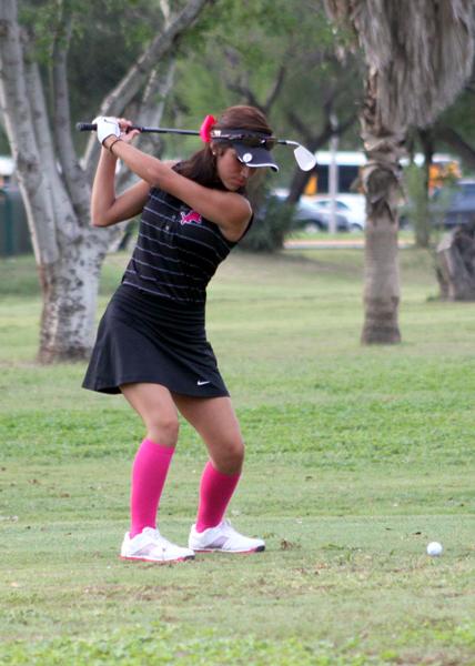 Celica Quintana hitting an iron off the fairway.