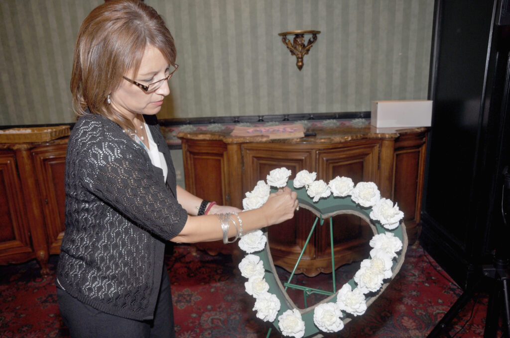 Katie McCarty, Director of Volunteer Services for Valley Baptist Health System, arranges white flowers on a heart-shaped wreath, in remembrance of babies who passed away before or shortly after birth, during an annual memorial service for grieving parents.