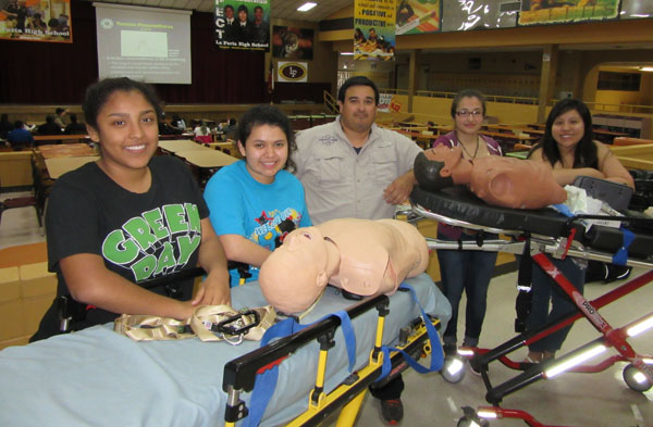Trained to be first on the scene of a school shooting with ambulance stretchers:  (l)  Naomi Reyes, Lluvia Perez, Instructor Joshua Alvarado, Leticia Garcia, Karynna Martinez.