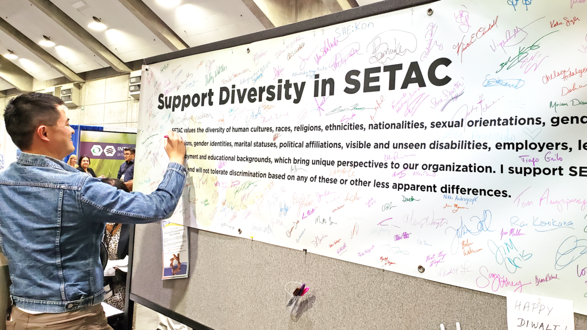 "Photo of Ben Young Landis, Creative Externalities. Photo by Sarah Stinson. The photo is of Ben signing a poster that reads ""Support Diversity in SETAC"" at the 2018 SETAC North America Annual Meeting."