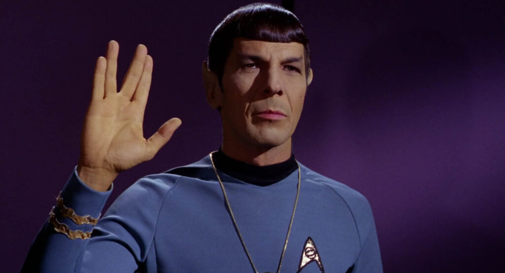 "Photo of Mr. Spock from Star Trek, holding his hand up in the Vulcan salute, with a ""V"" formed by parting his fingers."