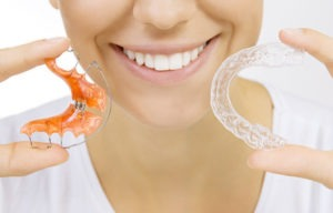 hands holding retainer for teeth and tooth tray