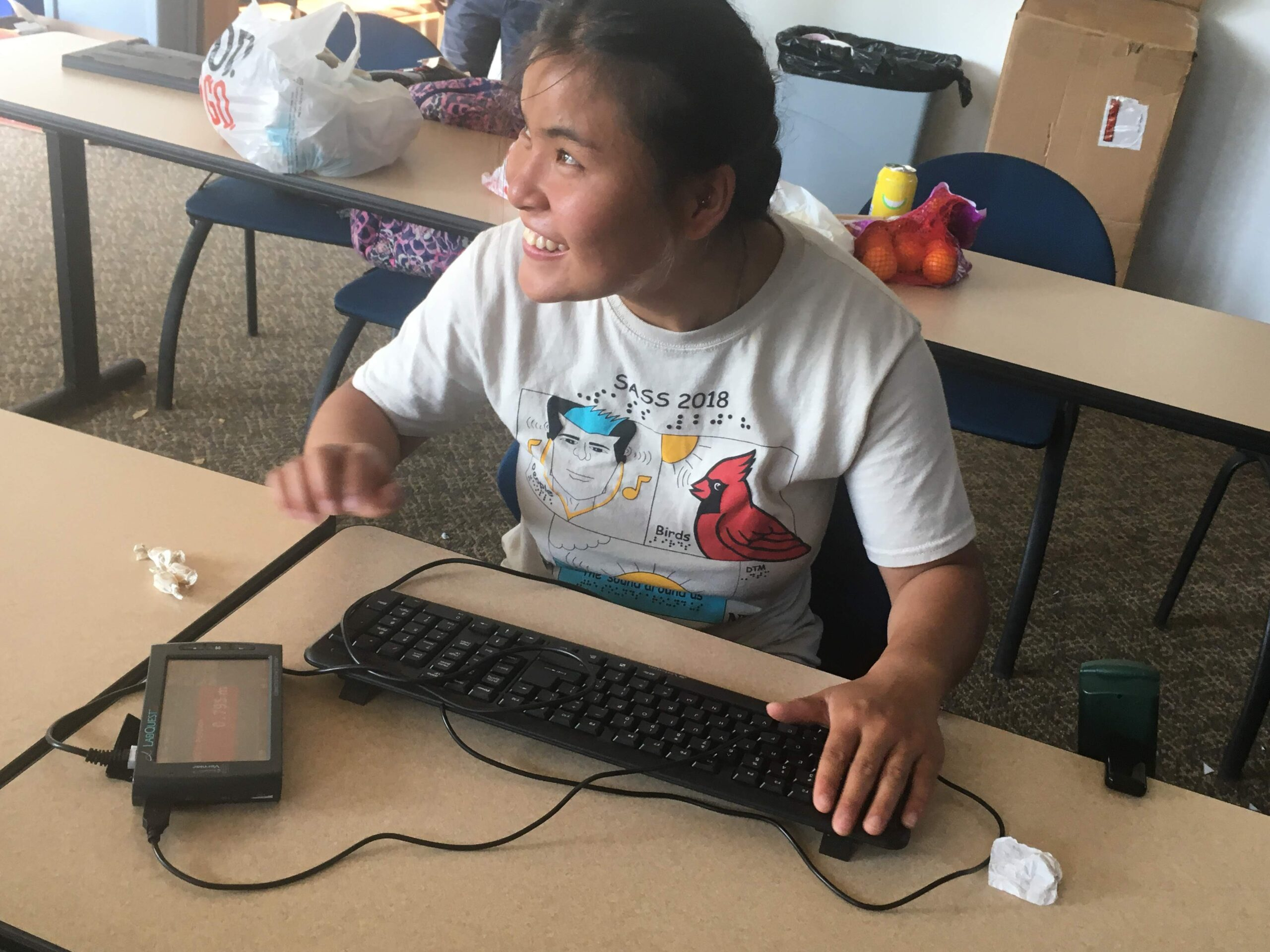 A student has a huge smile on her face while using the motion sensor with hand movement