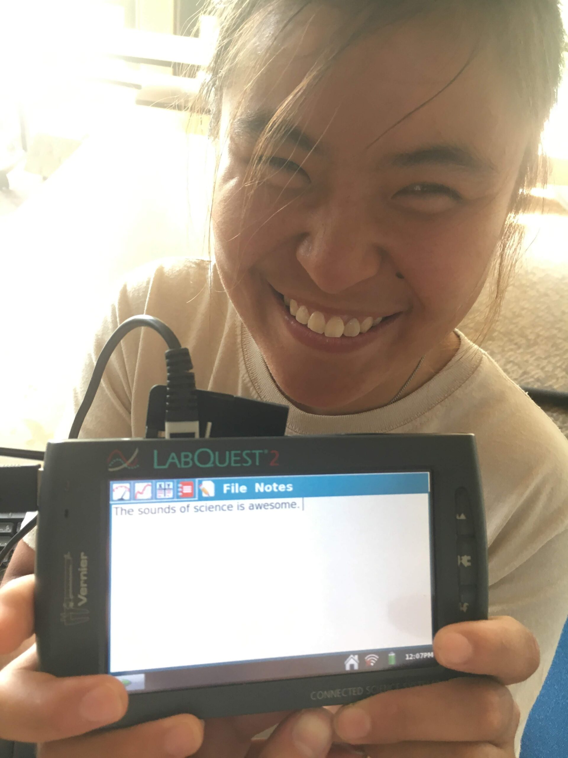 """A smiling student holds up a LabQuest notes page that reads """"The sounds of science is awesome."""""""