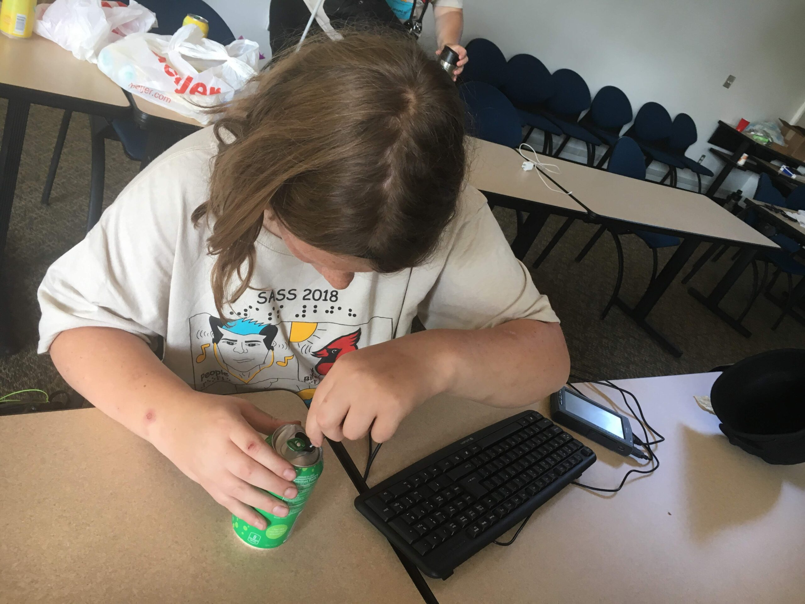 A student checking the temperature of a fizzy drink using LabQuest