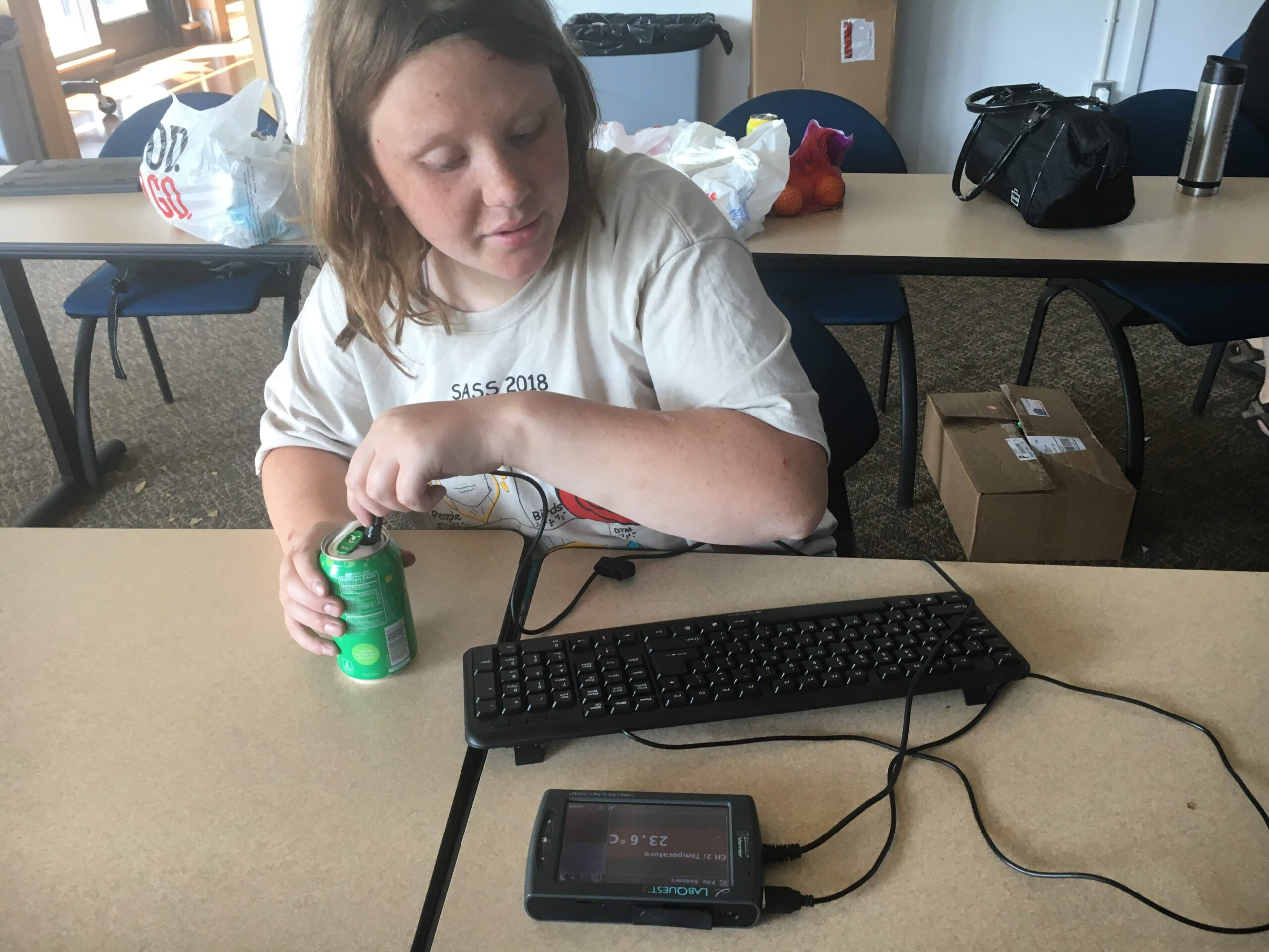 A student with a quizzical look on her face checking the temperature of a fizzy drink using LabQuest screen is shown with 23.5 degrees C displayed