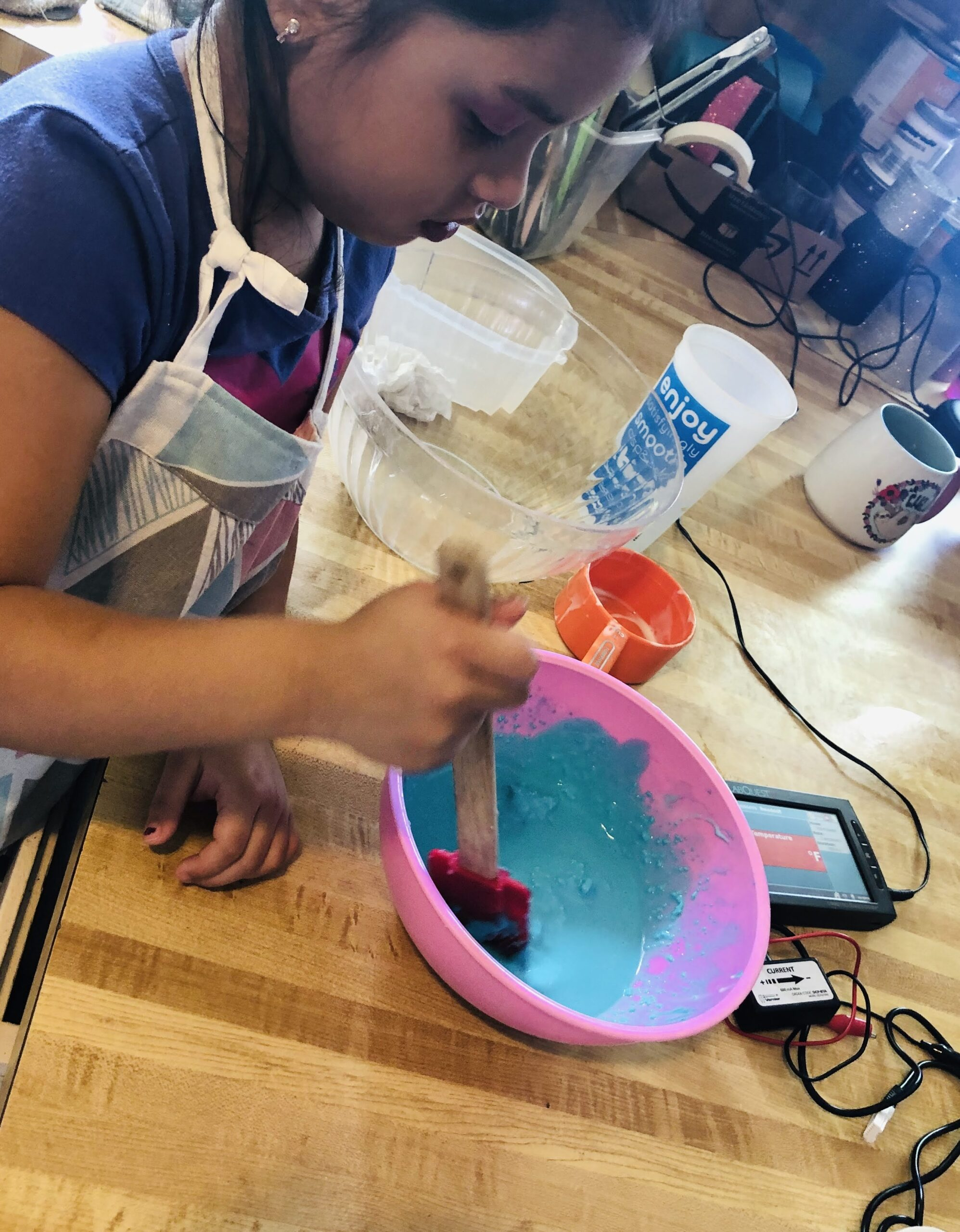 A young girl makes a blue slime mixture
