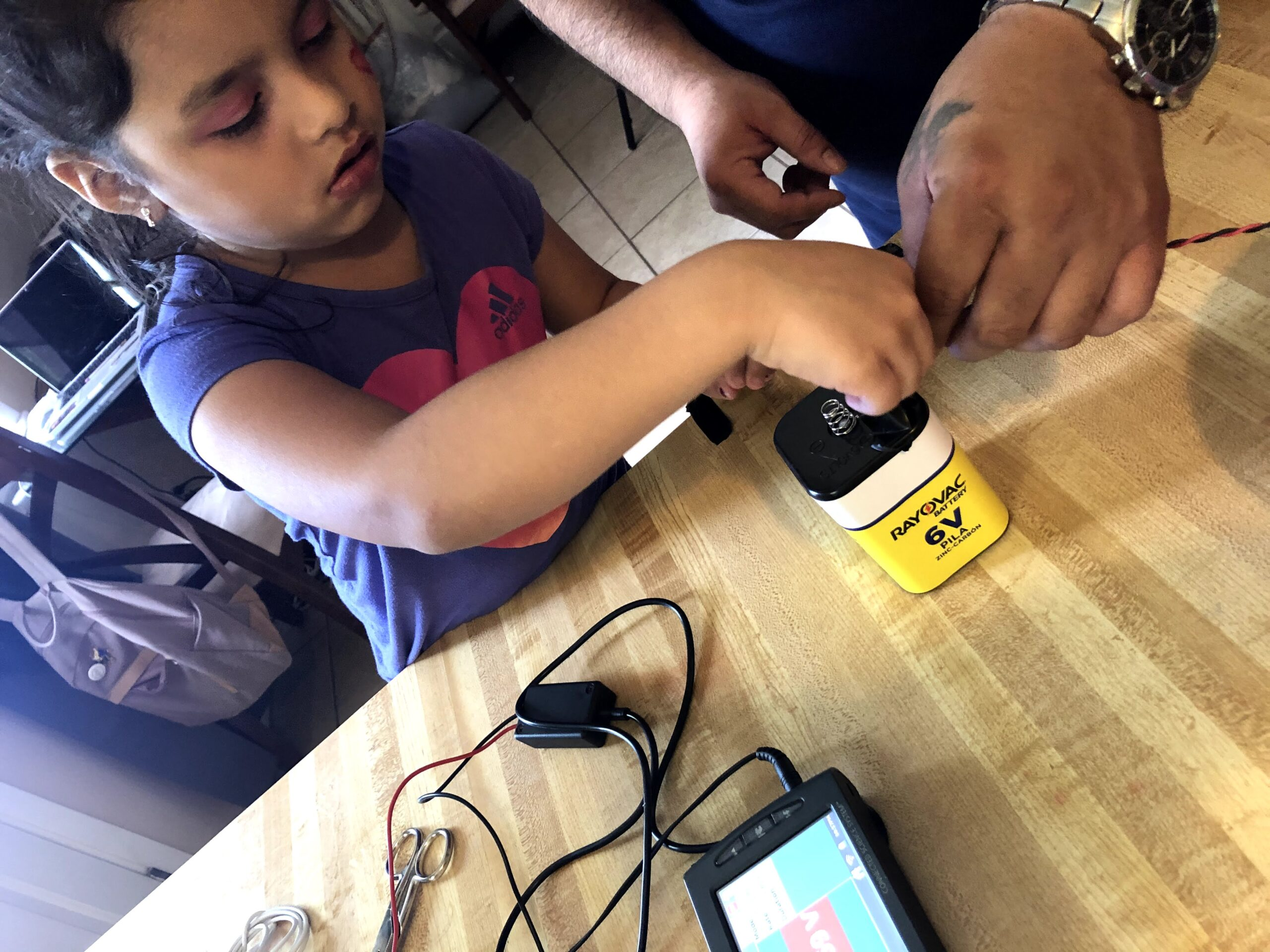 A young girl with her male guardian works with a wire experiment on a 6V battery