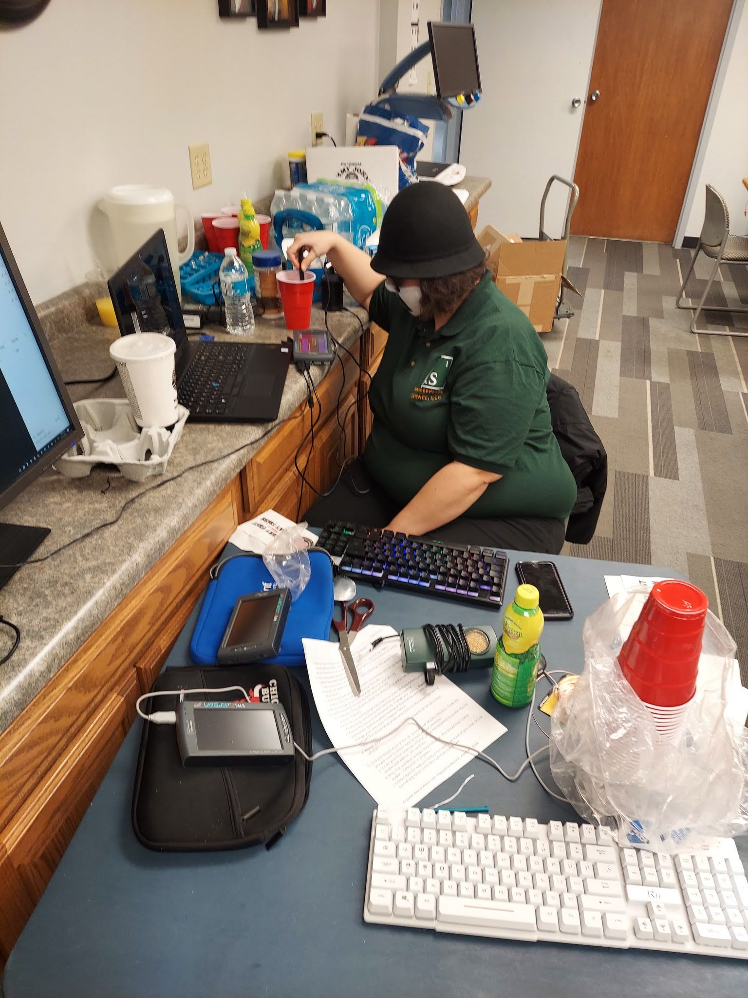 A socially distanced view shows Ashley stiring a cup of salted ice water with a temperature probe and the Talking LabQuest for a virtual demo wearing a matching Independence Science shirt and face mask