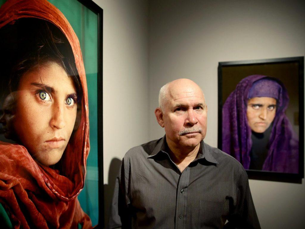 O fotógrafo Steve McCurry entre as duas fotos que fez de Sharbat Gula, uma quando ela era criança e anos depois quando a reencontrou adulta   Foto: Getty