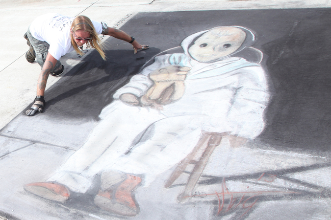 Sarasota based artist Stig Lindow is shown putting finishing touches on his 2013 Key West Chalk Festival creation, a larger-than-life rendering of Key West Art & Historical Society mascot, Robert the Haunted Doll.  Photo by Carol Tedesco