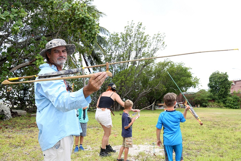 Instructor Lee Starling holds an atlatl as children participating in last week's Key West Art & Historical Society Native American Craftsman ArtCamp! practice throwing with the ancient tool that uses leverage to achieve greater velocity.