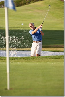 Senior Male Golfer Playing Bunker Shot On Golf Course