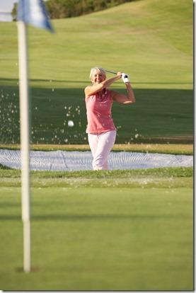 Senior Female Golfer Playing Bunker Shot On Golf Course