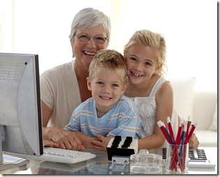 Happy children using a computer with their grandmother