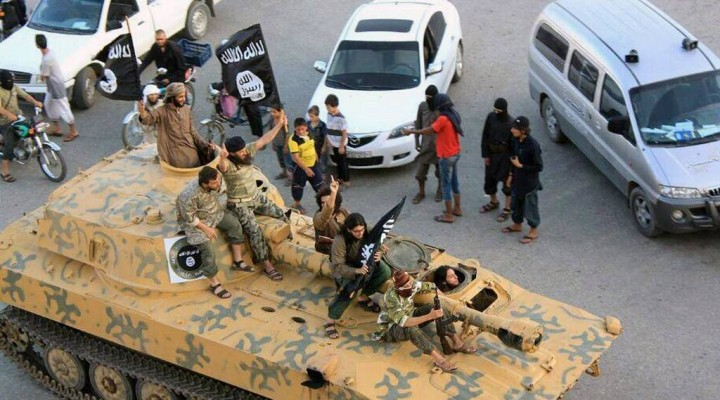 Fighters from Islamic State group sit on their tank during a parade in Raqqa, Syria