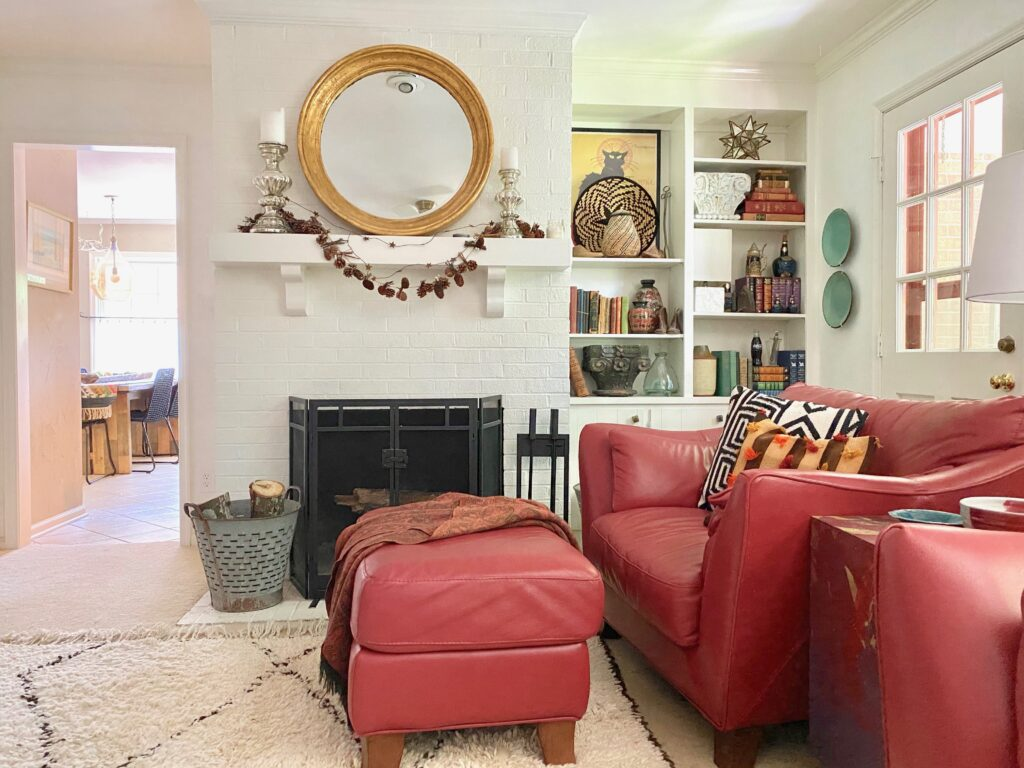 A Moroccan Beni Ourain rug softens a den full of red leather furniture.