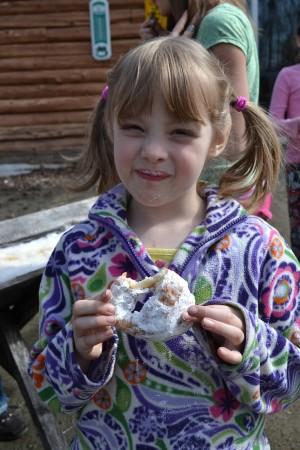 Chloe eating donut at sugar on snow