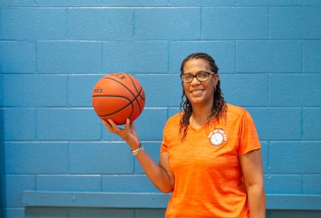 Coach Debbie holding a basketball