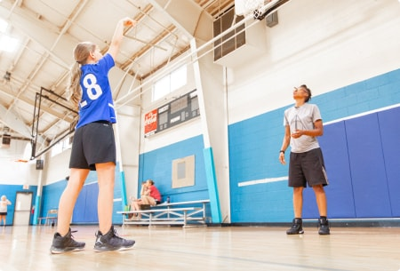girl practicing shooting drill with her coach