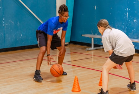 female player learning dribbling from her coach