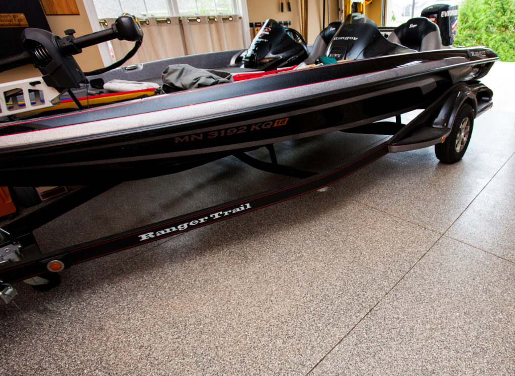 Our Industrial Flooring Products provide the perfect solution for a wide range of home applications. This image shows a boat trailer parked on our Vinyl Chip System system installed inside of a garage. These floors are tough and spill resistant, abrasion resistant and backed with a 15-year manufacturer warranty!