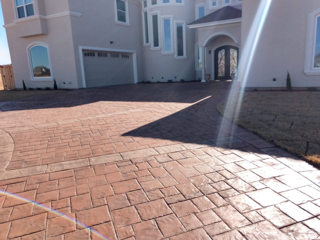 What else makes the entry into your home look better than a custom driveway? We love this stamped and stained concrete driveway! It adds a perfect accent to the gorgeous Spanish-style design on the exterior of this custom built home.